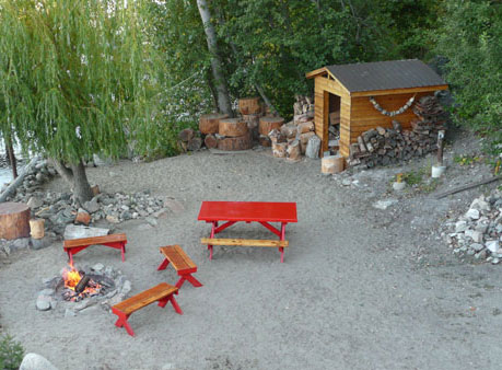 Sandy beach with table, seating, and firewood